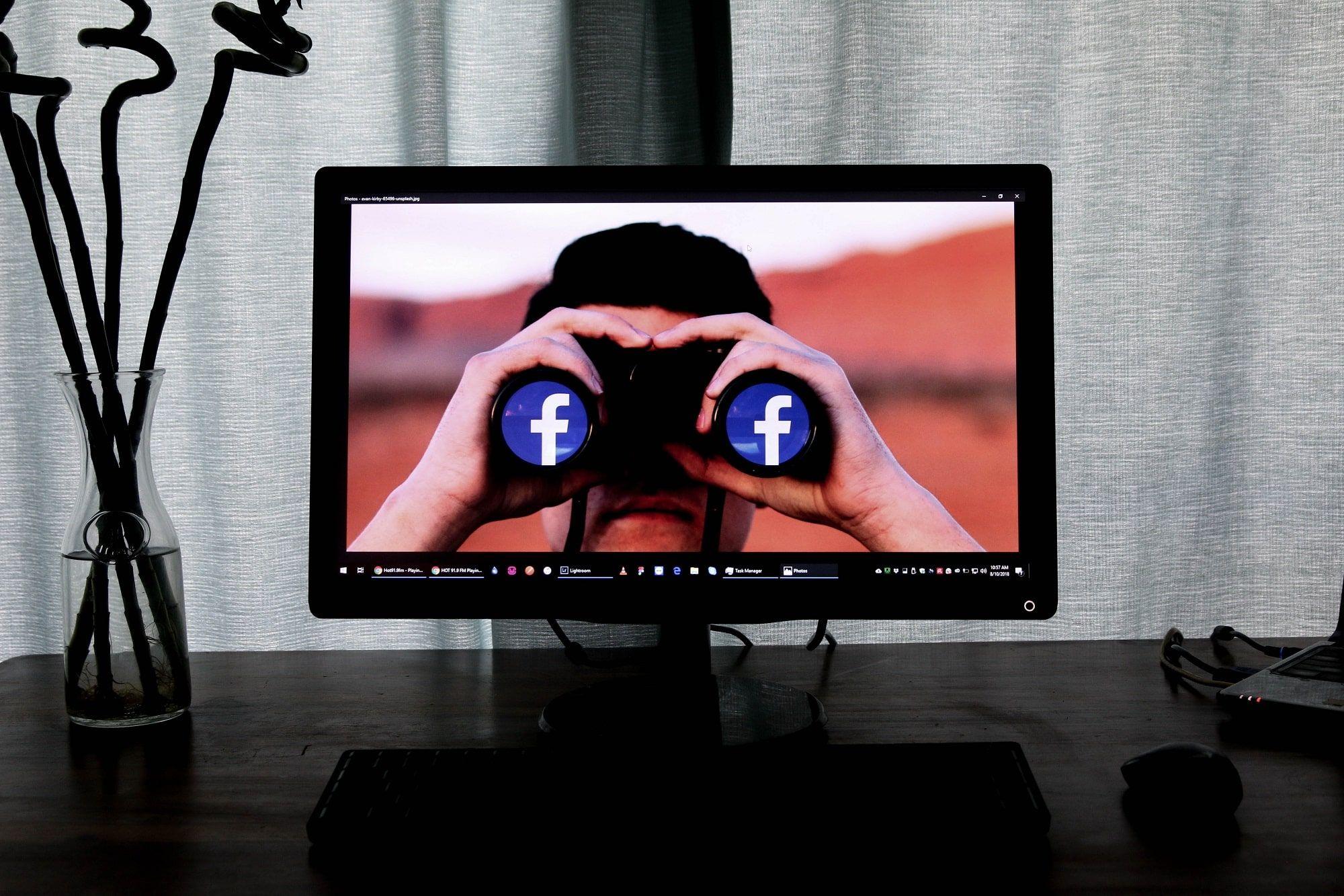 Person looking at Facebook in binoculars